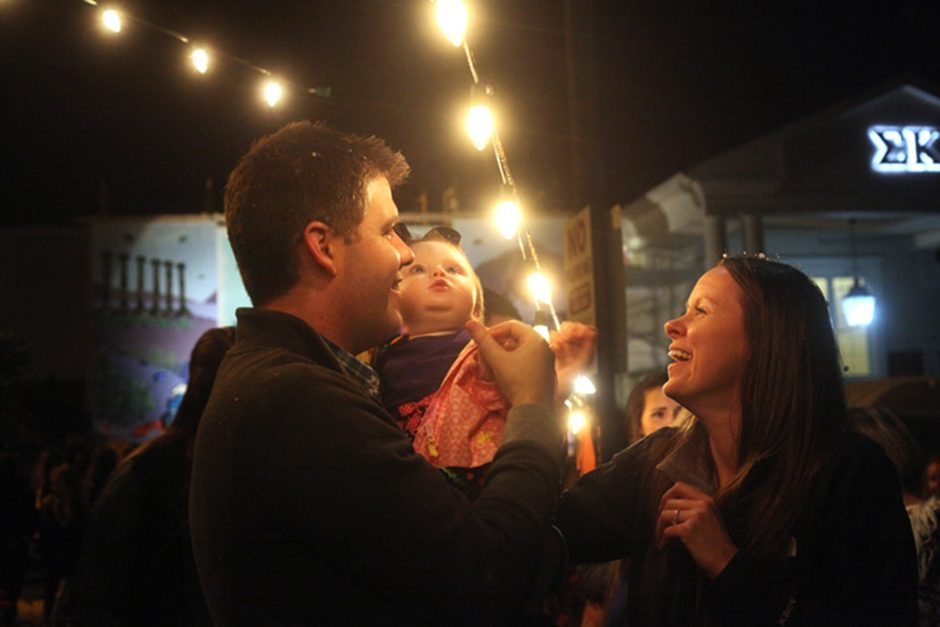Mike Puricelli and Elizabeth Puricelli laugh as their 11-month-old daughter, Annalise Puricelli, is mesmorized by the Christmas lights hanging outside of Chi Omega sorority during the homecoming house decoration showcase on Friday, Oct. 22, 2016.