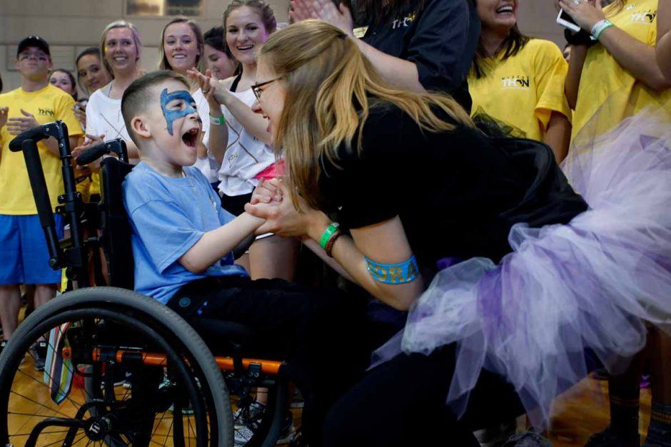 Child in wheelchair wearing face paint, smiling and holding hands with a Mizzou student.