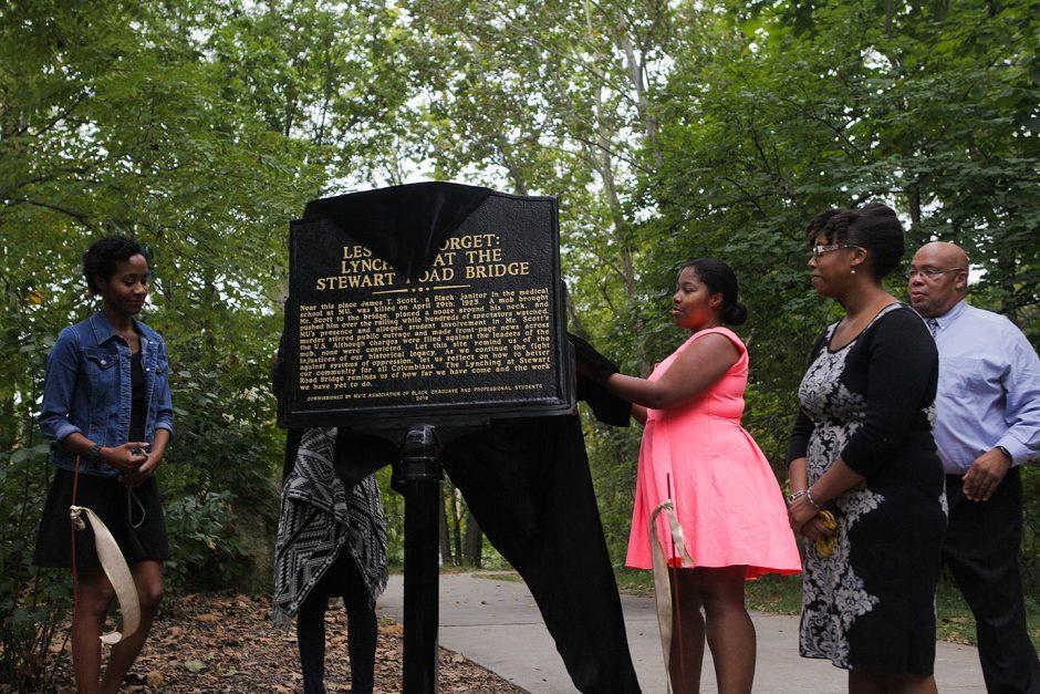 Community members unveil marker.