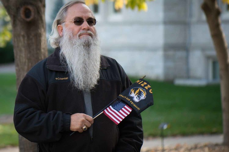 Man with grey beard holding flags.