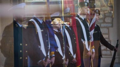 Members of Mizzou's ROTC are reflected in the glass doors under Memorial Union's archway.