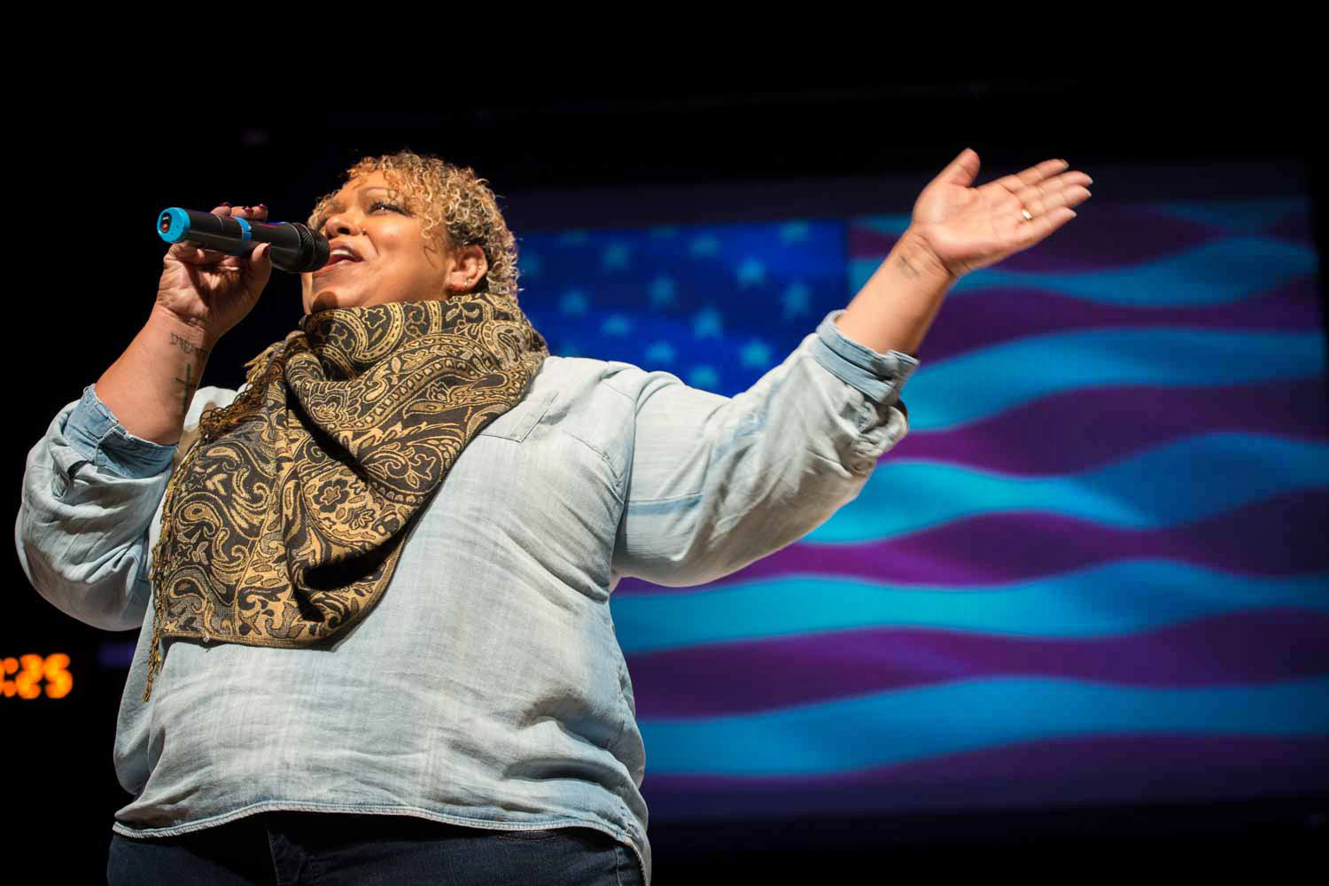 Cathy Cox, mother of Olympic medalist J'den Cox, sings the National Anthem on Jesse Auditorium's stage.