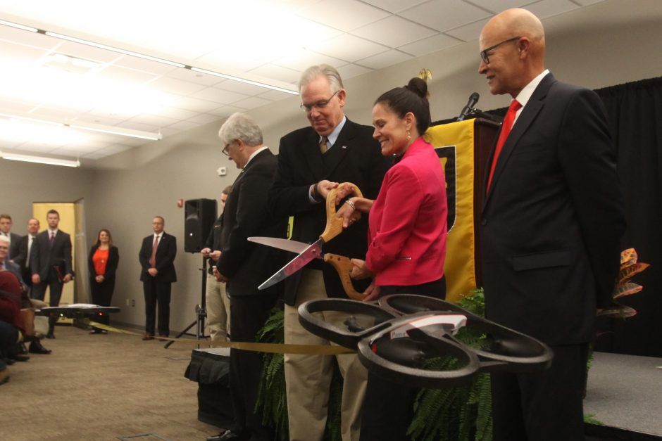 People with giant scissors cutting a ribbon.
