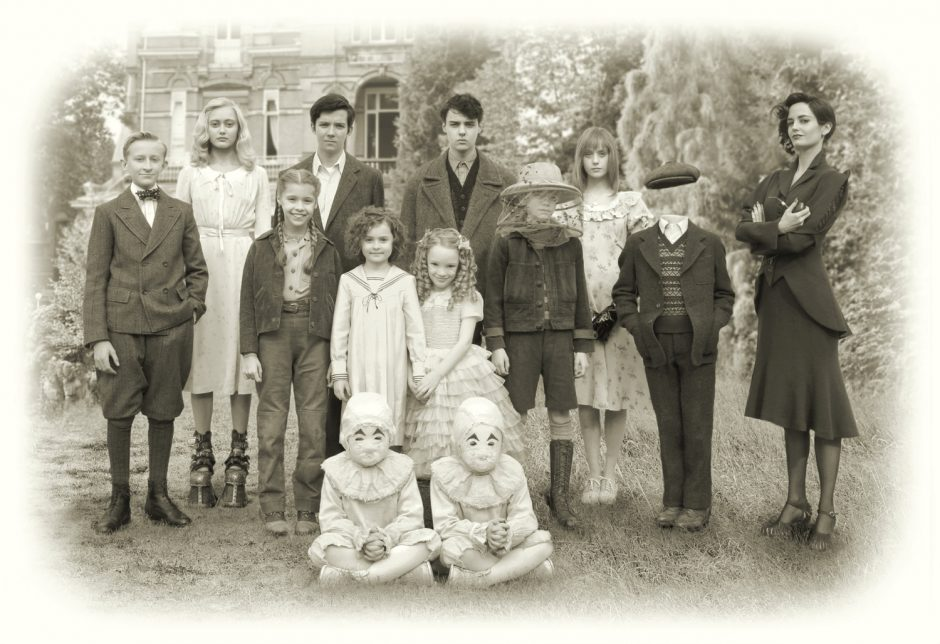 Old-timey photo showing a group of odd children in front of a house.