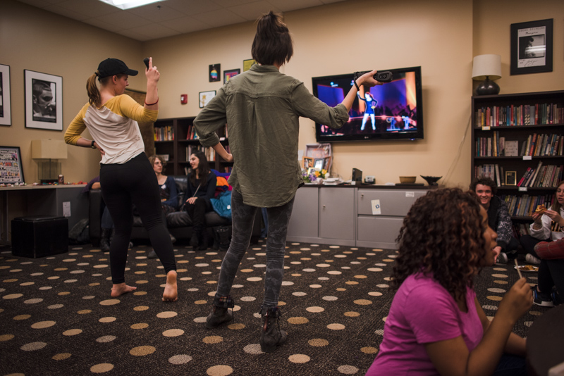 Students dancing in front of a video game screen.