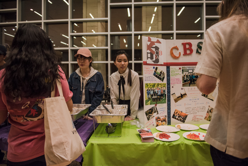 Students at a table with Chinese food and a poster display.