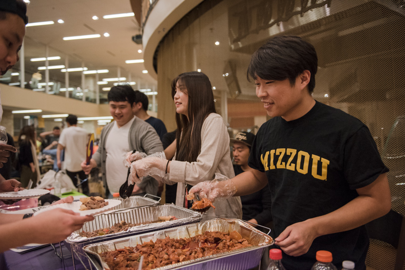 Students dishing out food for guests.