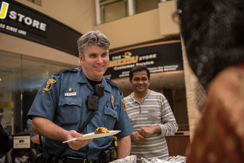 Police officer with a plate of food smiling at a student.