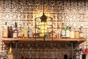 Bronze light fixture hanging in front of the bar.
