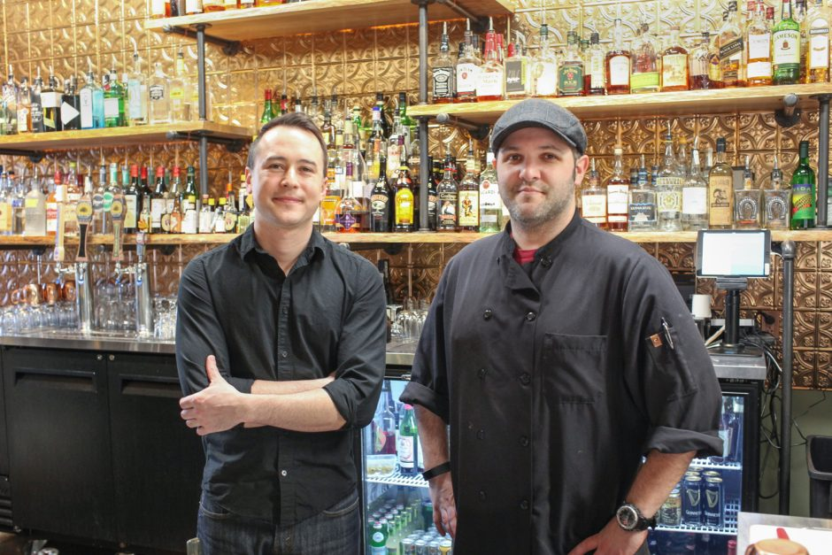 Two men standign in front of a bar.