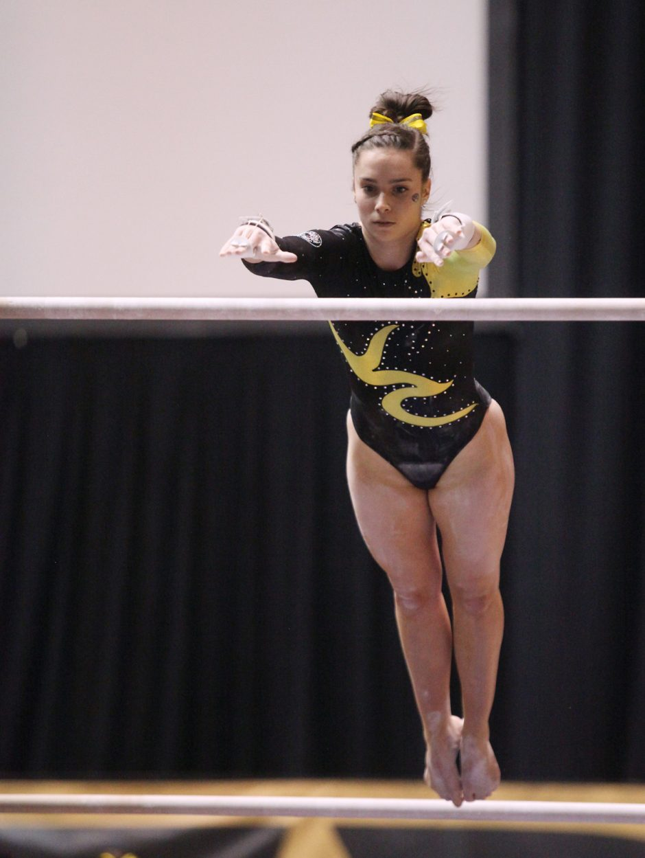 Gymnast peforming on uneven bars.