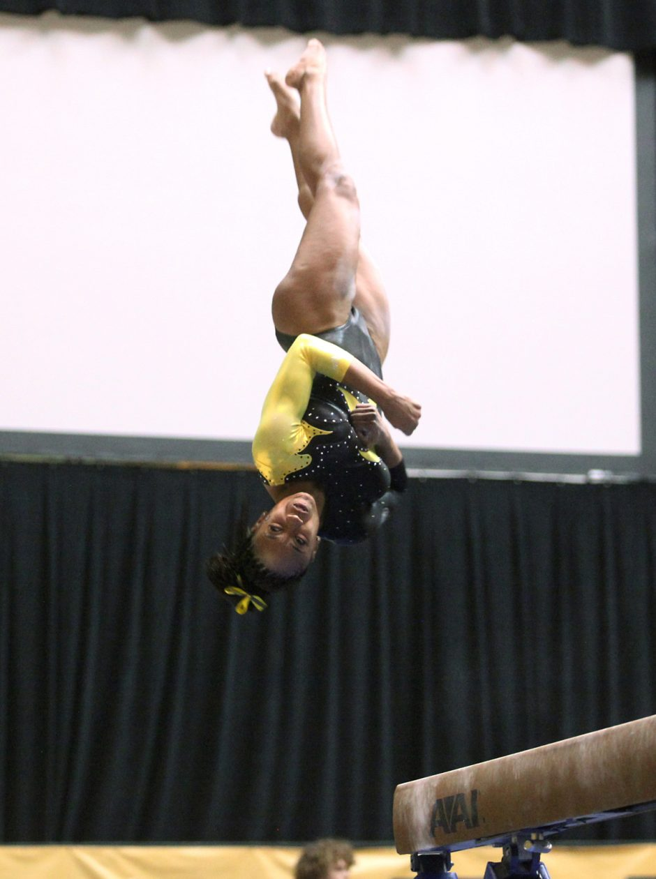 Gymnast spinning in the air upside-down.
