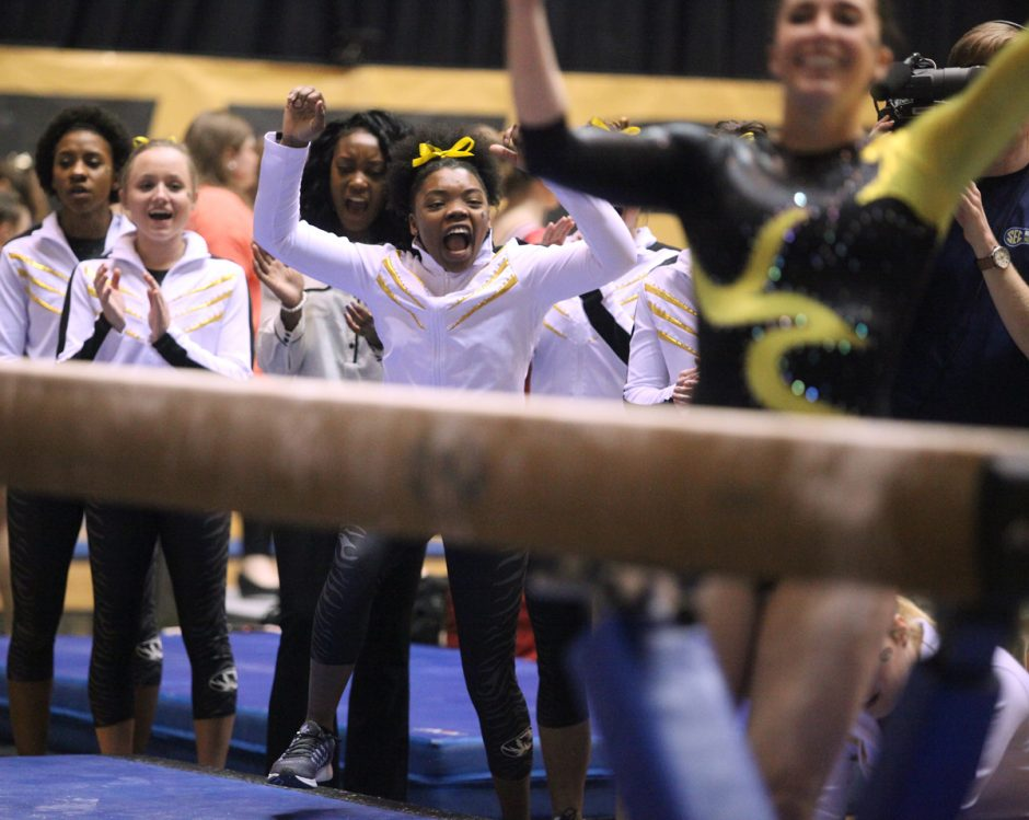 Gymnasts in warmup suits cheer as a teammate dismounts from the beam.