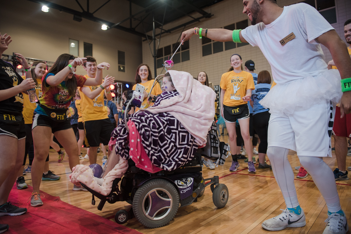 Man dressed in tutu holds a wand over girl in wheelchair's head as other students dance around them.