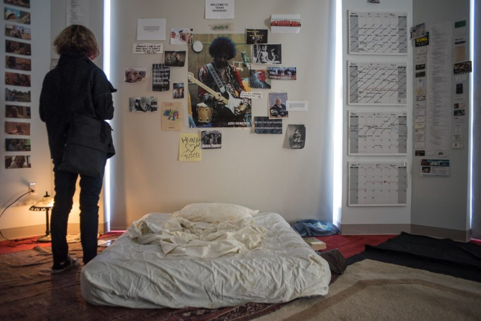 Photos of Jimi Hendrix, calendars and other papers on a wall over a mattress.