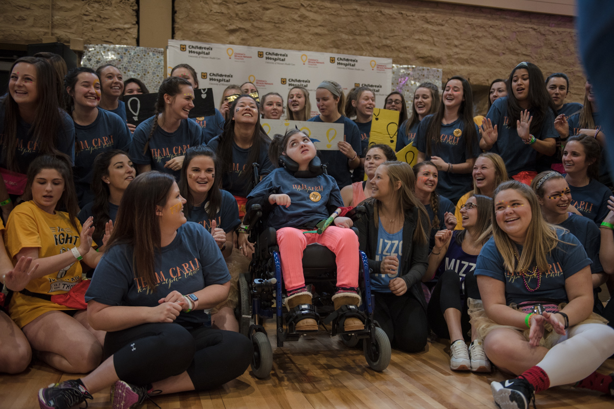 Women pose around girl in wheelchair