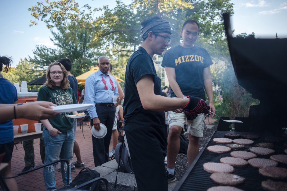 Students grilling burgers while other wait in line.
