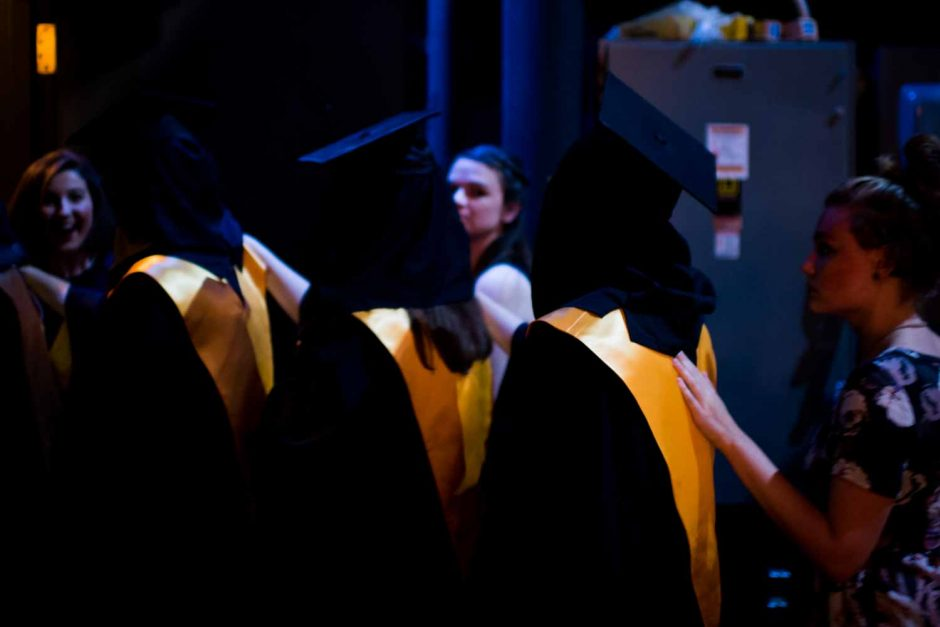 Members of Mortar Board, a national honor society that recognizes college seniors for their achievements in scholarship, leadership and service, are led to their seats in Jesse Hall before Tap Day ceremonies begin.