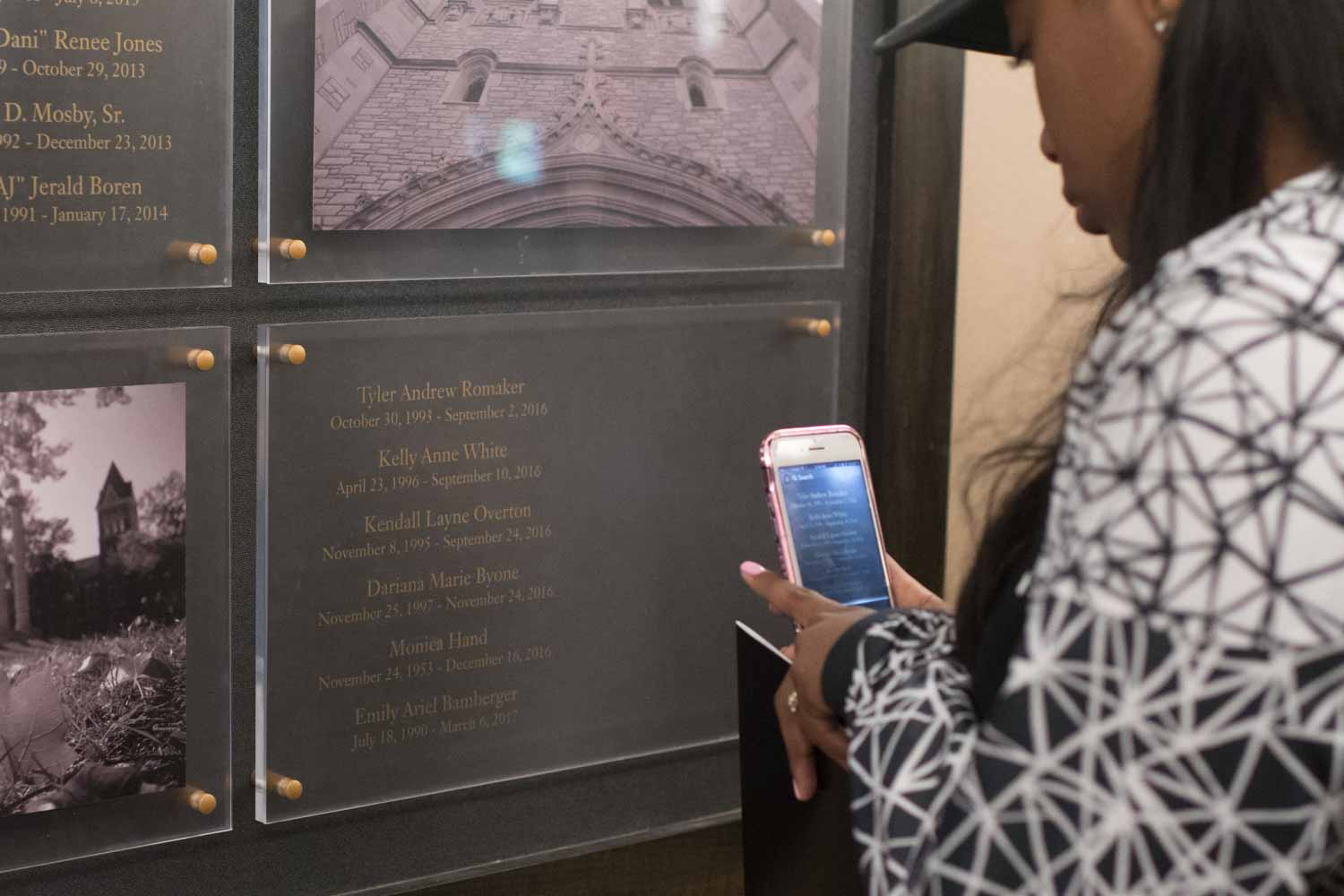 Raven Smith takes a picture with her cell phone of Dariana Byone's name, engraved on a plaque inside of Memorial Union, along with other students who have passed away.