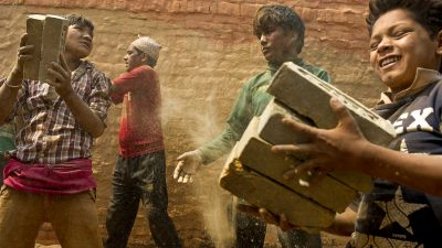 Young boys help stack bricks inside a kiln in Dhading district, Nepal in April, 2016. Despite a national law that bans children under the age of 14 from working, such scenes are commonplace in the country's brick making industry. This story was funded by the Pulitzer Center on Crisis Reporting. Photo: Ann Hermes/The Christian Science Monitor