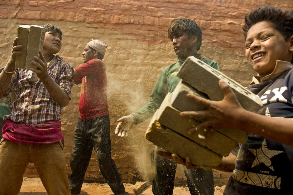 Young boys help stack bricks inside a kiln in Dhading district, Nepal in April, 2016.