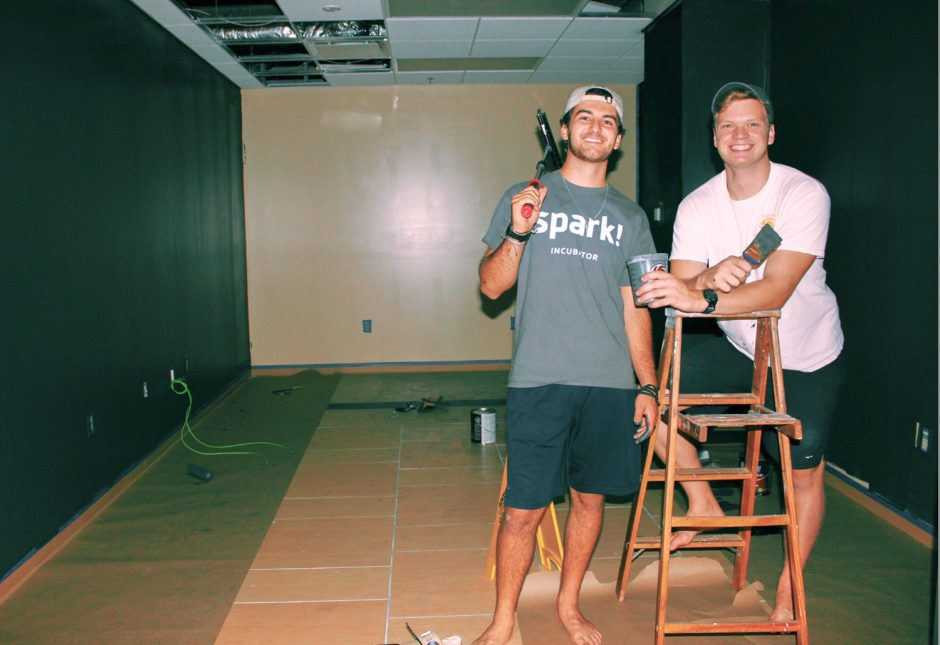 Drew Rogers and Blaine Thomas holding tools in an empty room.