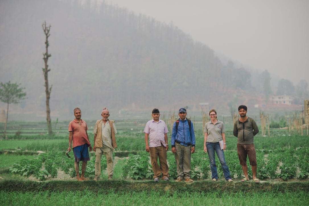 Woman standing in group in field with workers in Indonesia.