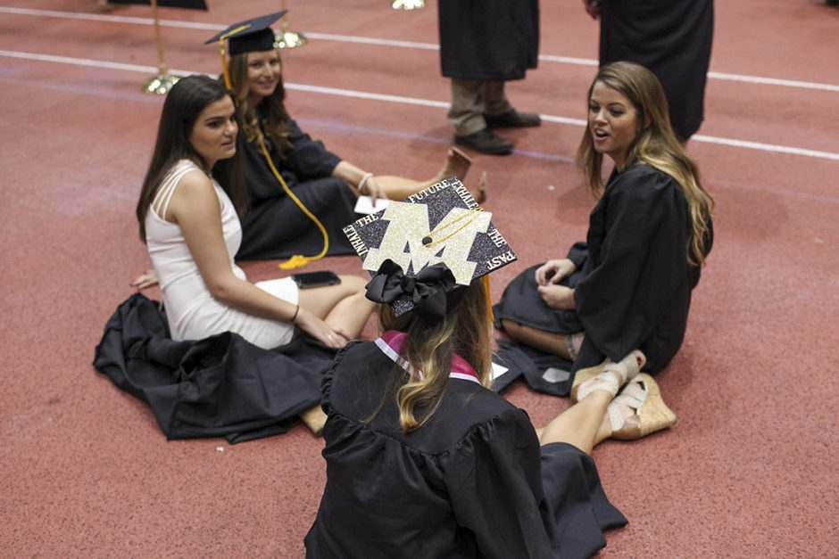 Women sitting on floor in caps and gowns.