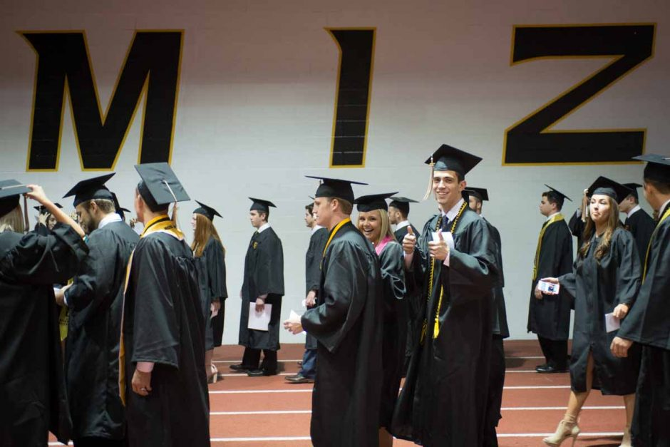 Students in caps and gowns walking together.