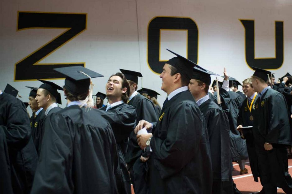 Students in caps and gowns walking together and laughing.