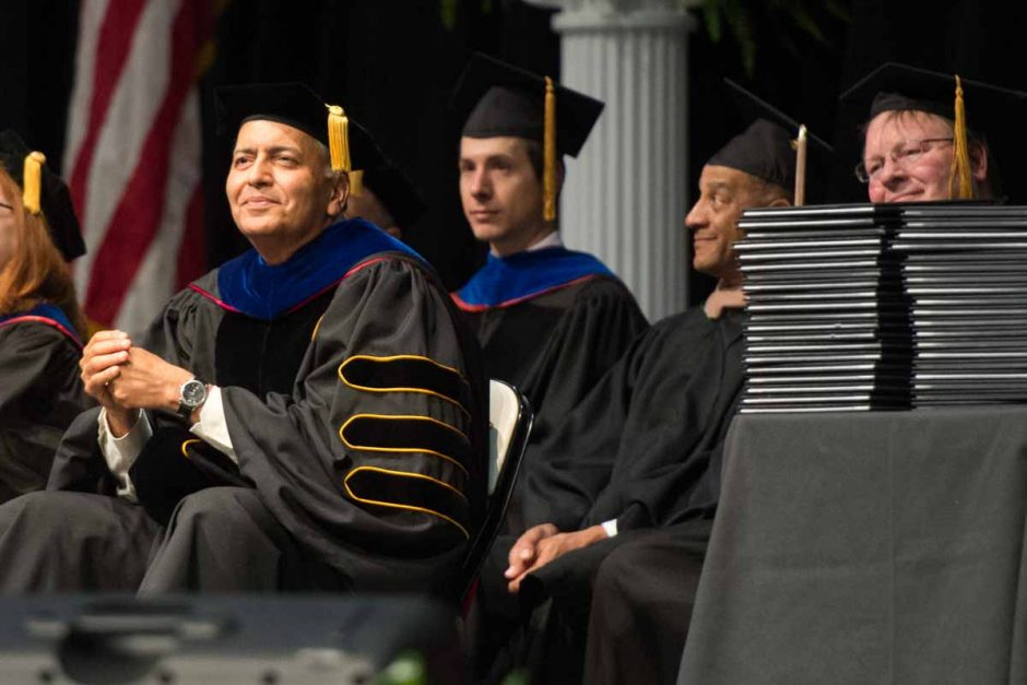 Dean seated next to stack of diplomas.