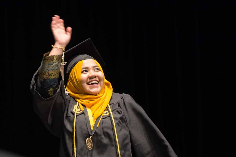 Woman in cap and gown and gold head scarf.