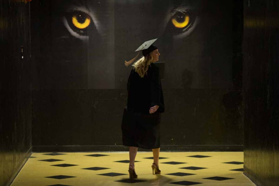 Woman in cap and gown walking in front of tiger eyes.