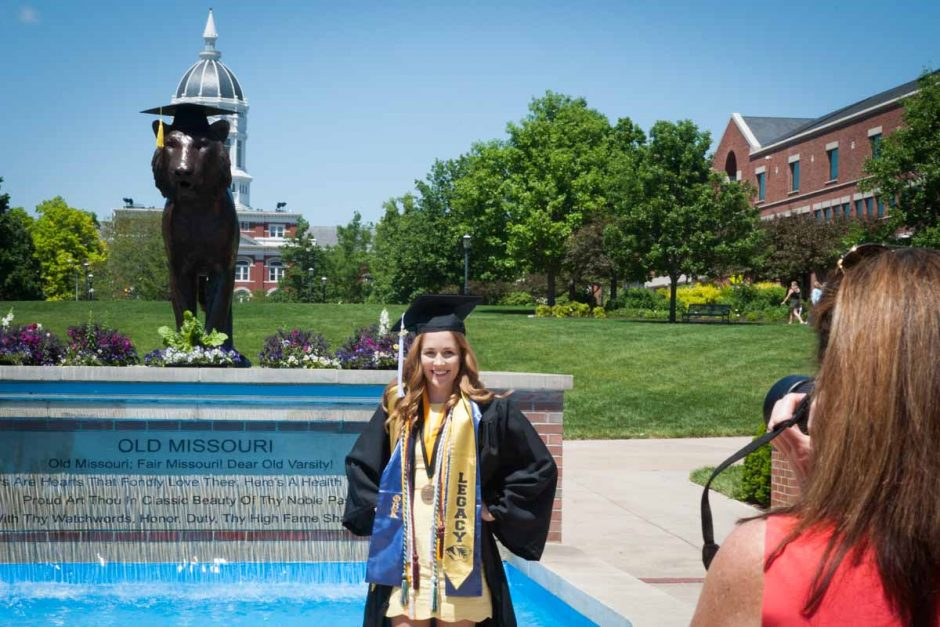 Woman in cap and gown in front of the fountain.