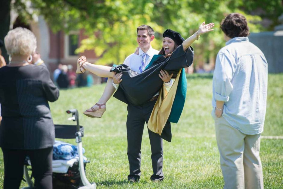 Man picking up woman in a cap and gown.