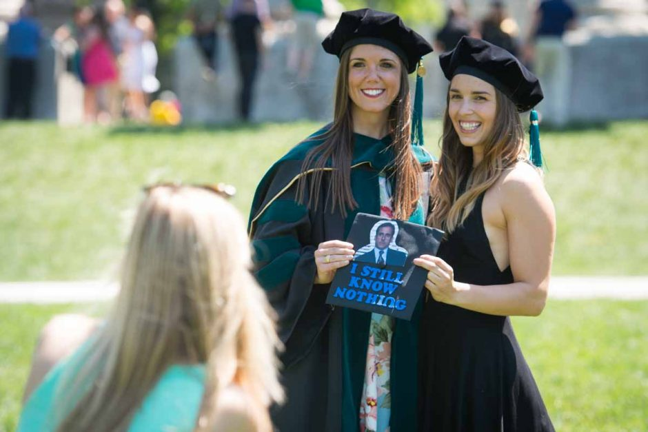 "Two students holding cap that says ""I still know nothing"" with photo of Michael Scott from ""The Office."""
