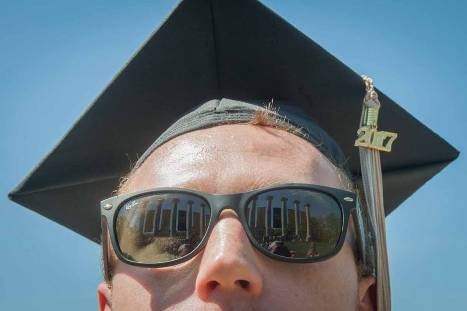 Student in cap and gown with columns reflected in sunglasses.