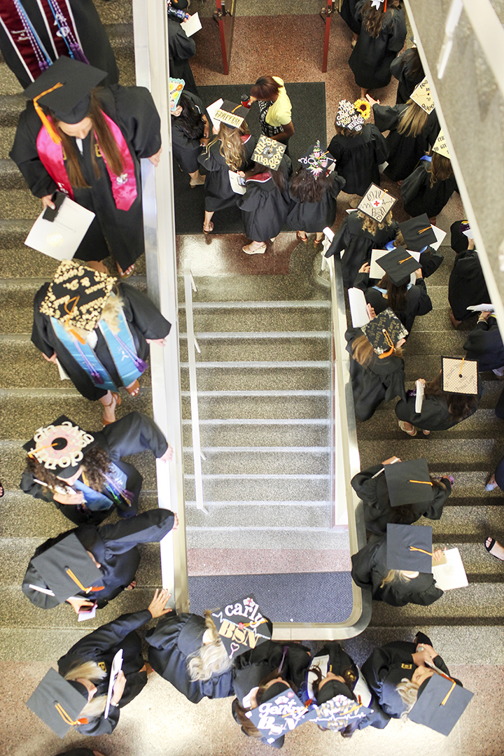 Students in caps and gowns walking down stairs.