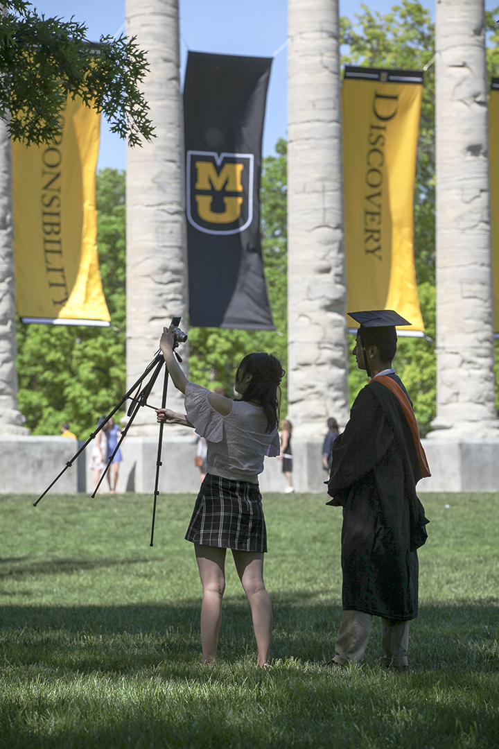 Student with camera on tripod next to the Columns.
