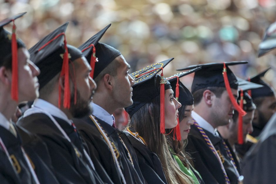 Students in caps and gowns looking to the left.