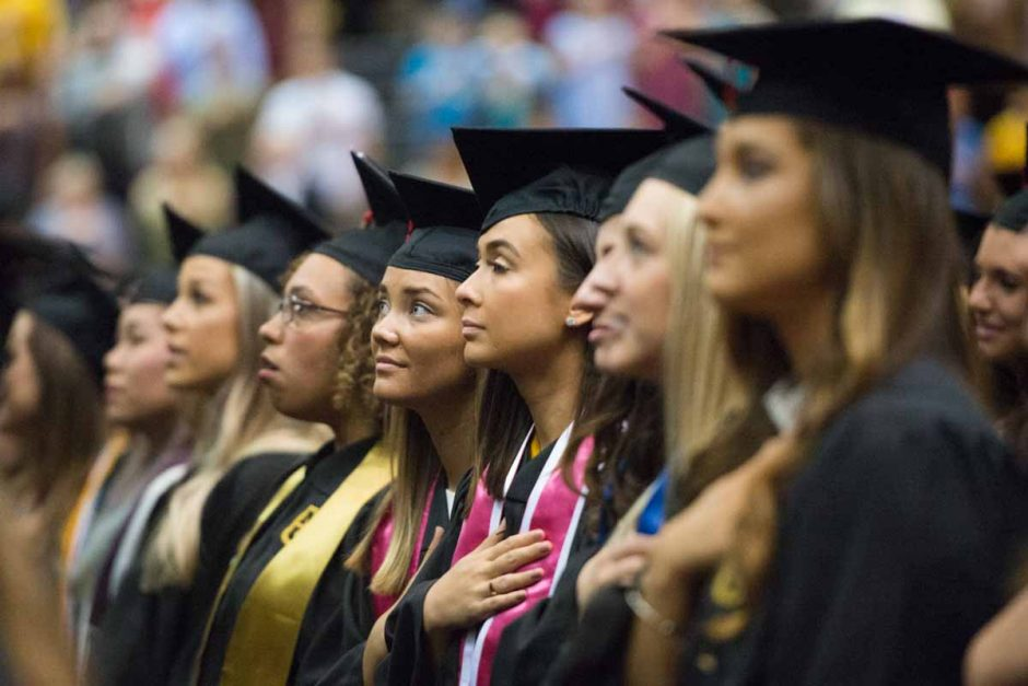 Students in caps and gowns with hands over their hearts.