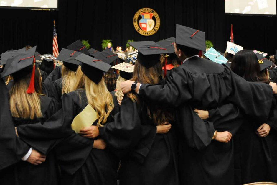 Students in caps and gowns with arms around each other.