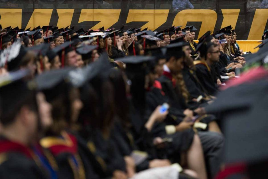 Students in caps and gowns seated.