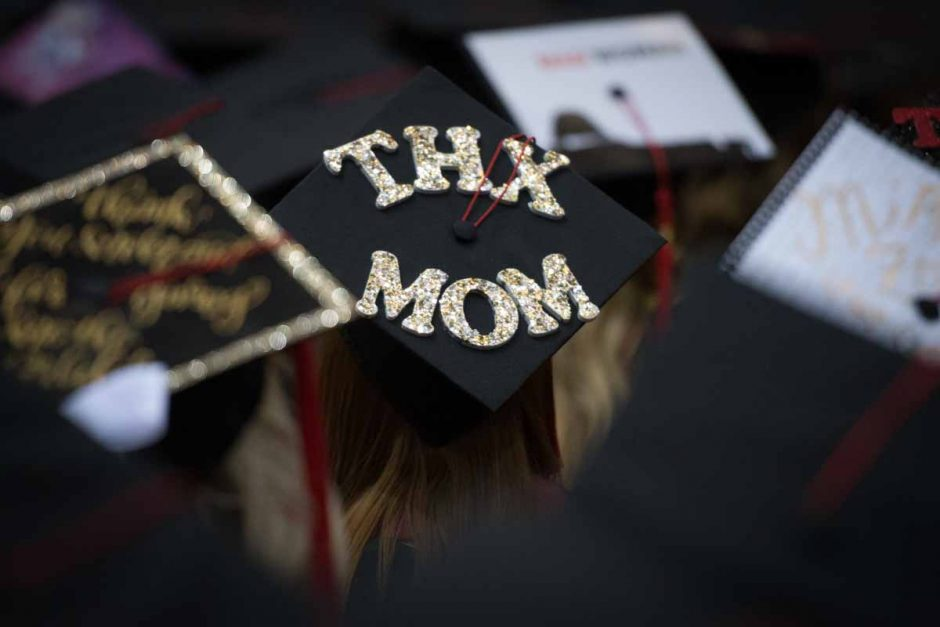"Student in cap that says ""THX MOM"" in glitter letters."