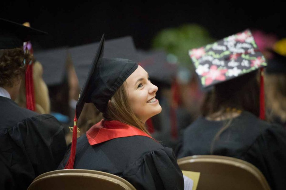 Student in cap and gown smiling.