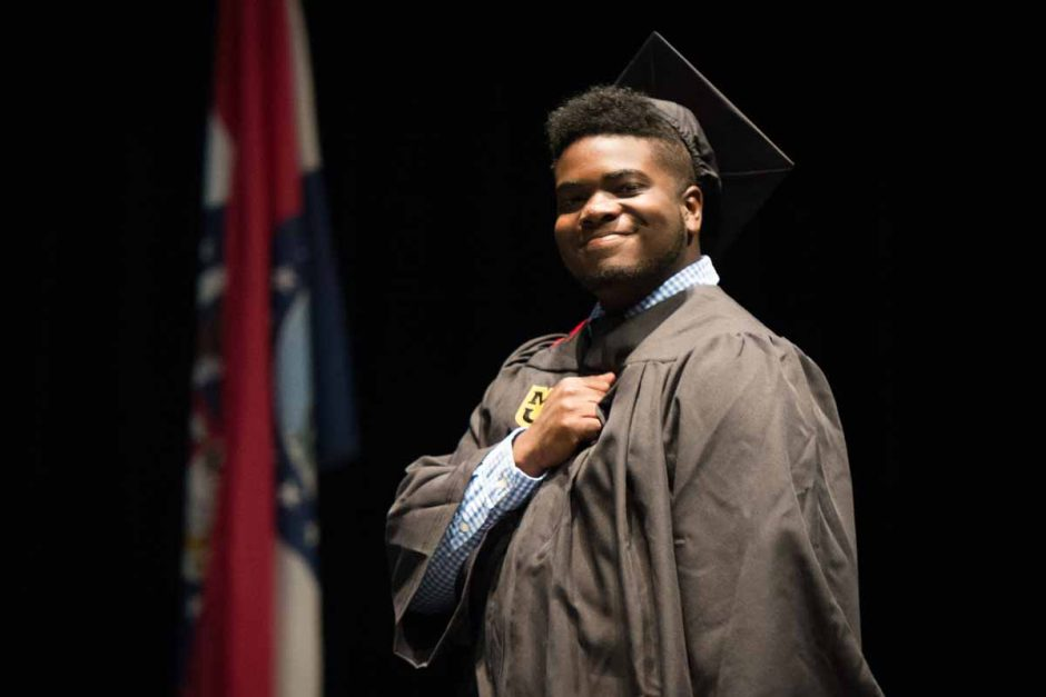 A journalism graduate celebrates on stage by placing his fist on his heart. Photo by Shane Epping.