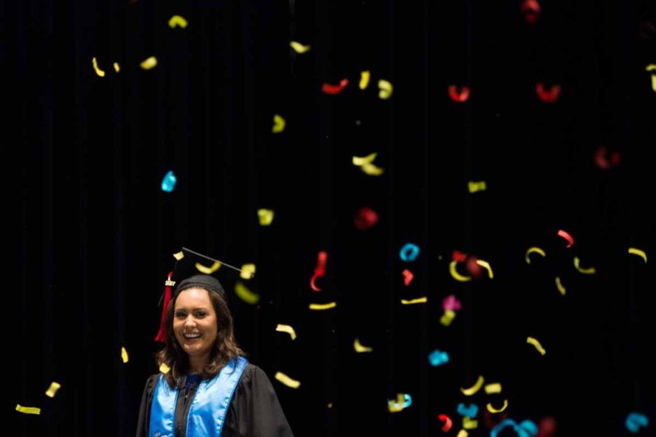 Woman in cap and gown surrounded by confetti.