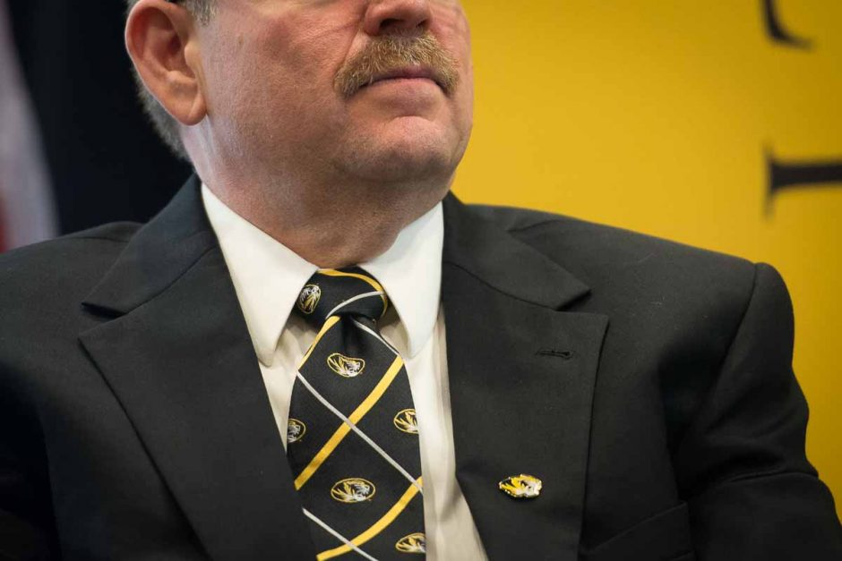 Chancellor Alex Cartwright sports a black and gold tie and lapel pin.