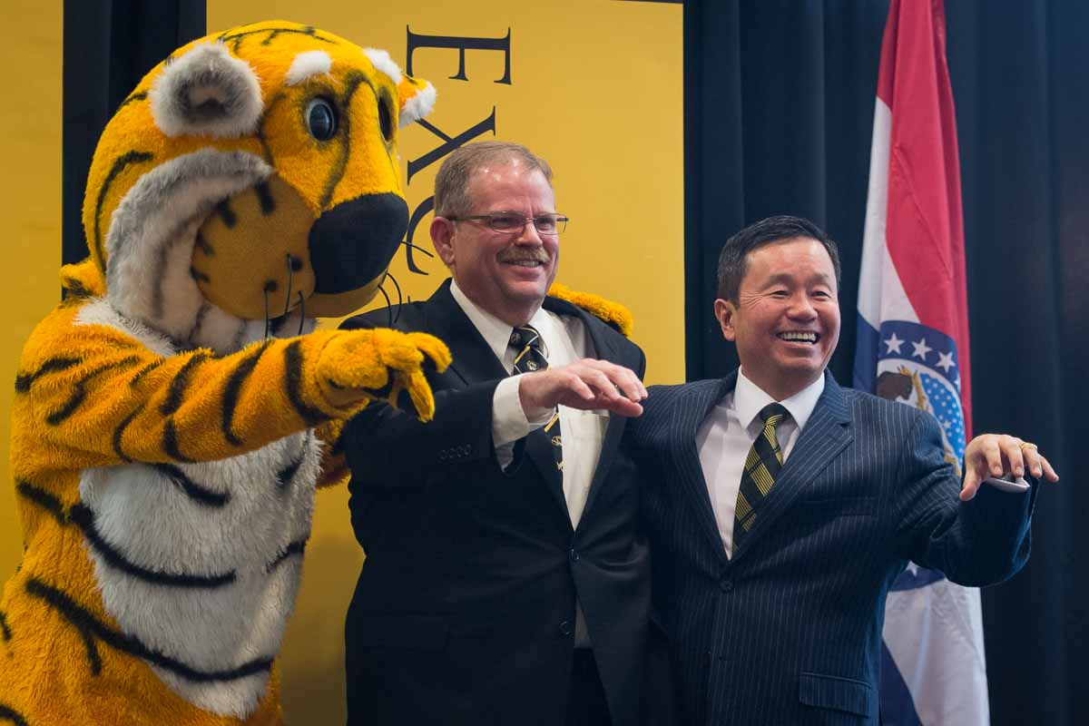 """Truman, Chancellor Alex Cartwright, and President Mun Choi show off their """"paws"""" at the end of the press conference where Cartwright was officially welcomed to the Mizzou community."""