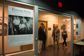 "People standing outside the exhibit space for ""Possum Town."""